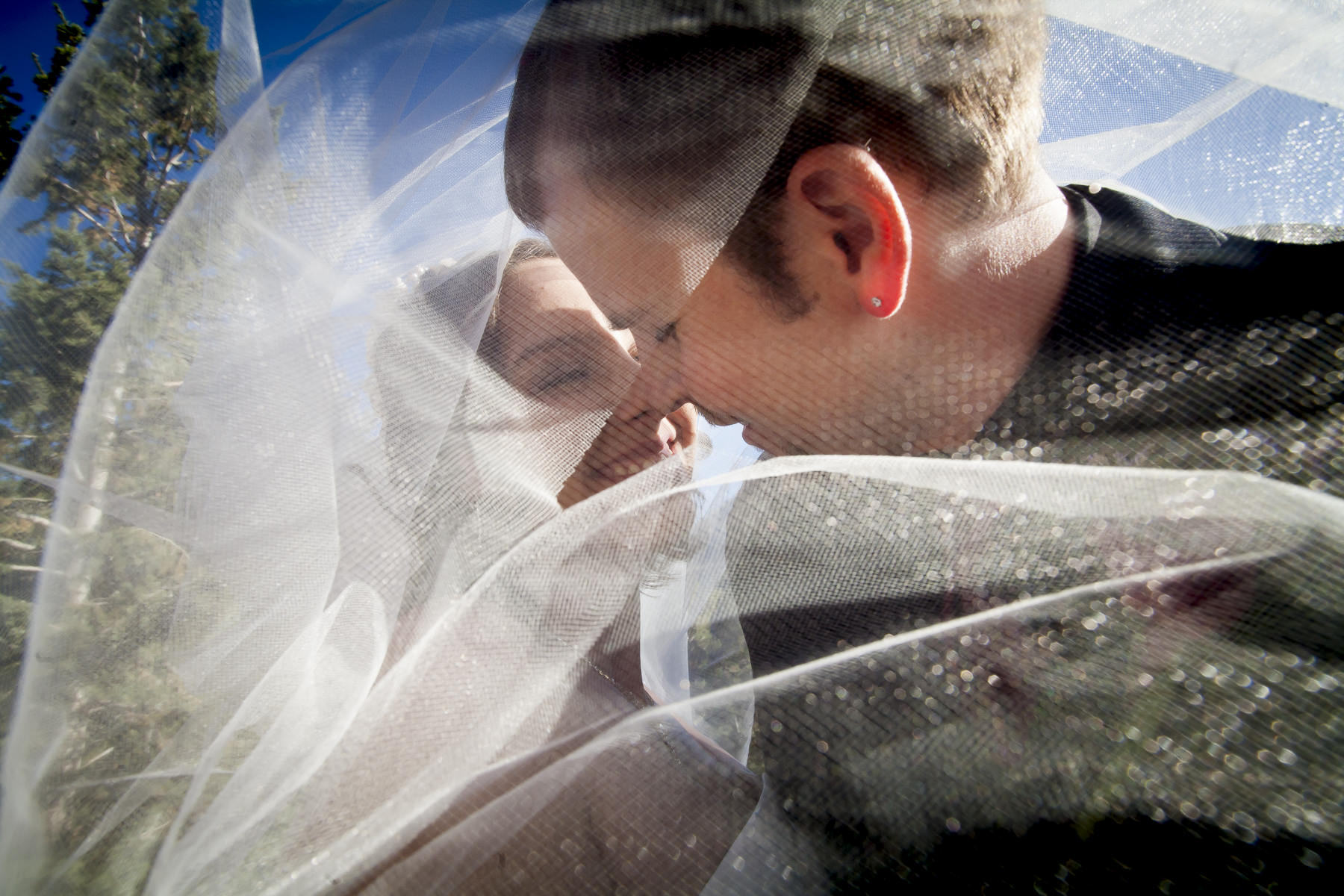 Bride and groom underneath wedding veil with smiling.