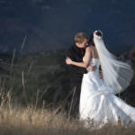 Bride and groom embrace in a field.