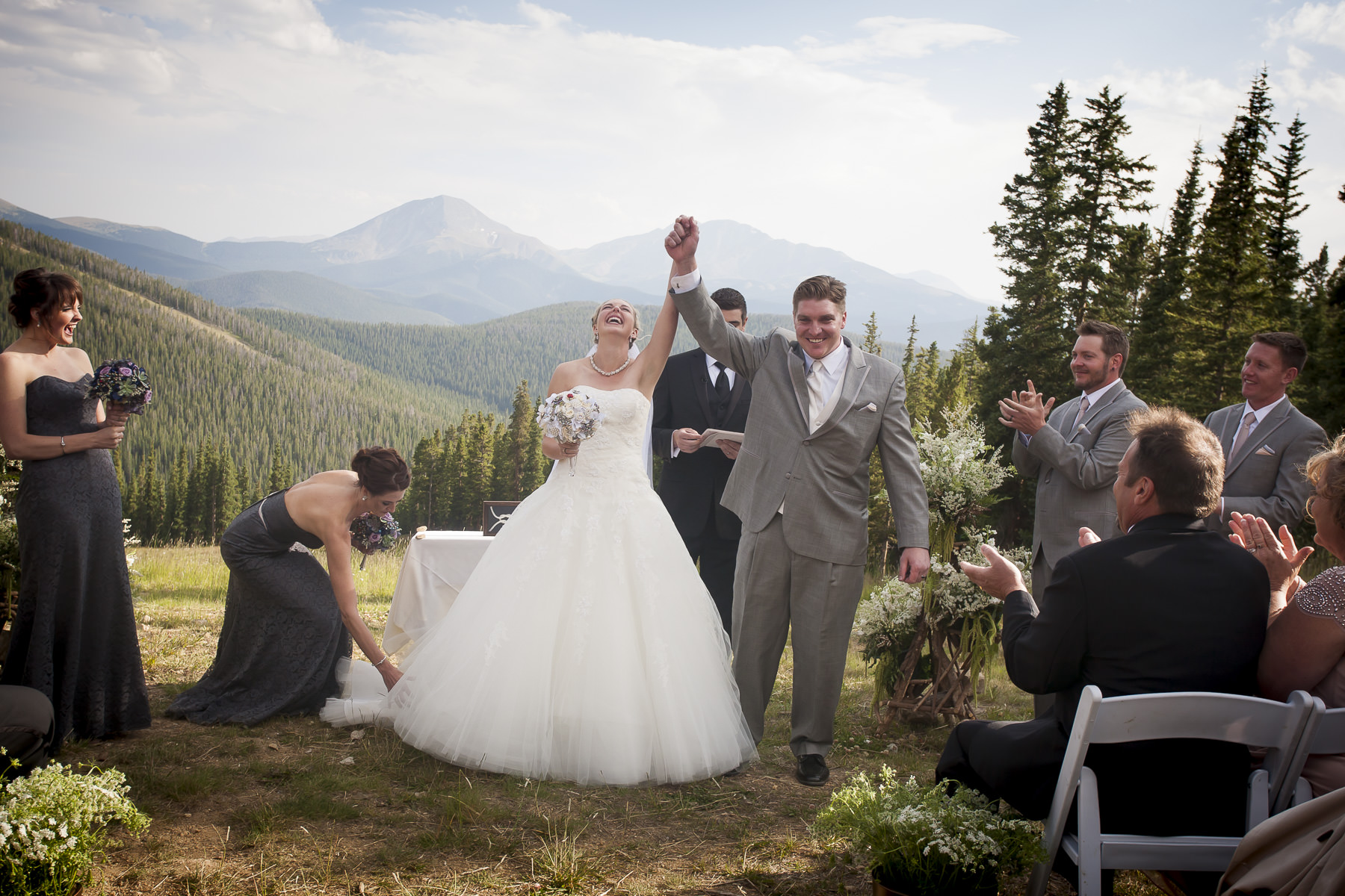 Bride and groom raise their hands into the air at the conclusion of their wedding ceremony at Peak 7 at Keystone Resort.