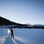 Bride and groom kissing in the snow at Dillon Reservoir.