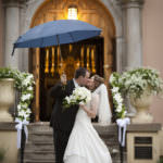 Bride and groom kiss underneath umbrella in front of Pauline Memorial Chapel.