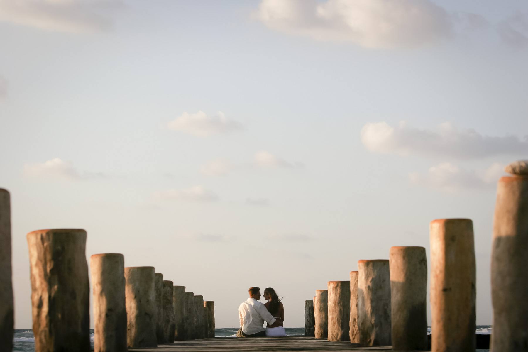 Man and woman sit together on ocean pier.
