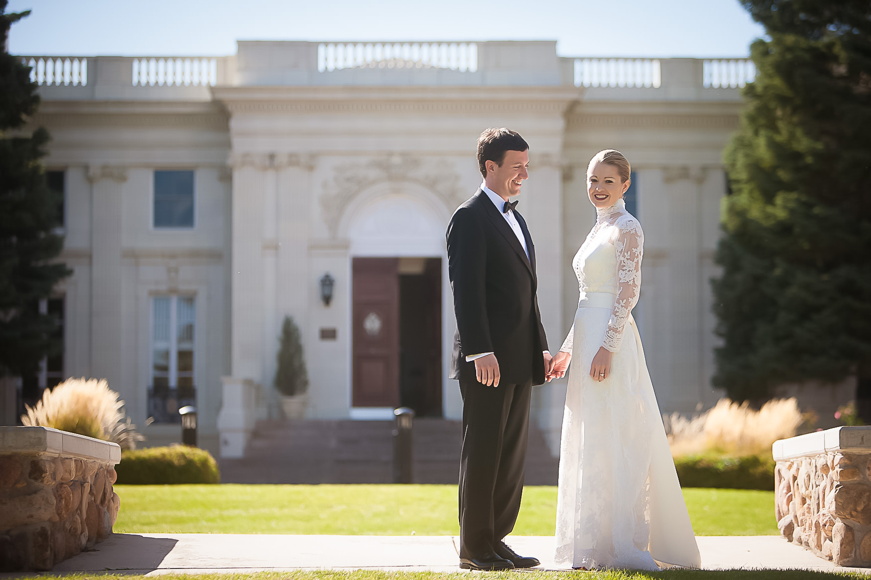 Bride and groom stand in front of the Trianon at the Colorado Springs School.
