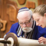 Girl and Rabbi read Torah during Bat Mitzvah ceremony at Temple Shalom.