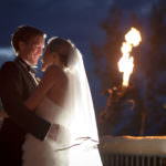 Night shot of bride and groom embrace in front of torch at the Cheyenne Lodge.