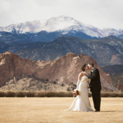 Bride and groom kissing in front of Garden of the Gods park and a snow covered Pikes Peak.