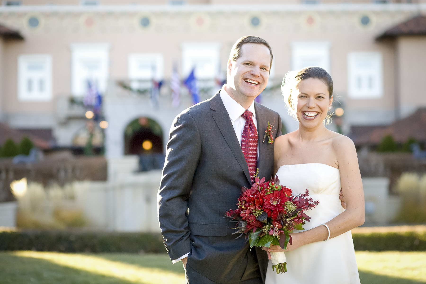 Bride and groom with red flowers, wedding dress and suit in front of the entrance to The Broadmoor.