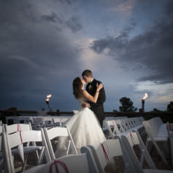 Bride and groom share a kiss outside by their ceremony site with torches at sunset at Cheyenne Lodge.