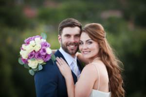 Bride and groom smiling and looking at camera with purple and white rose wedding bouquet.