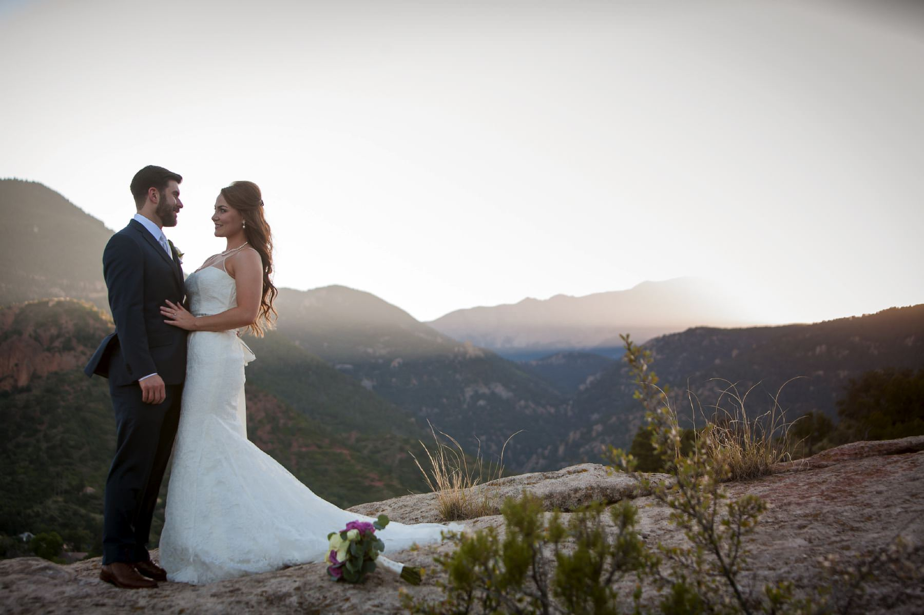 Bride and groom standing on rock with Pikes Peak in the background at sunset.