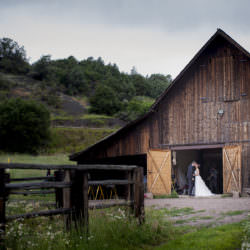 Bride and groom kiss in the doorway of a barn.