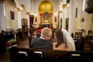 Bride and groom sitting in pew inside Pauline Memorial Chapel after their wedding.
