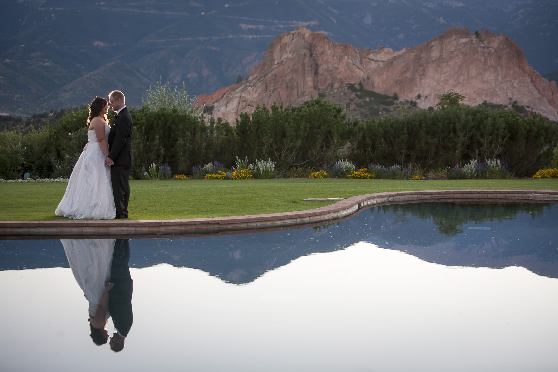 Bride and groom embracing in front of the reflection pool at sunset at the Garden of the Gods Club.