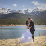 Bride and groom embrace in front of Crystal Lake and a snow-capped Pikes Peak.