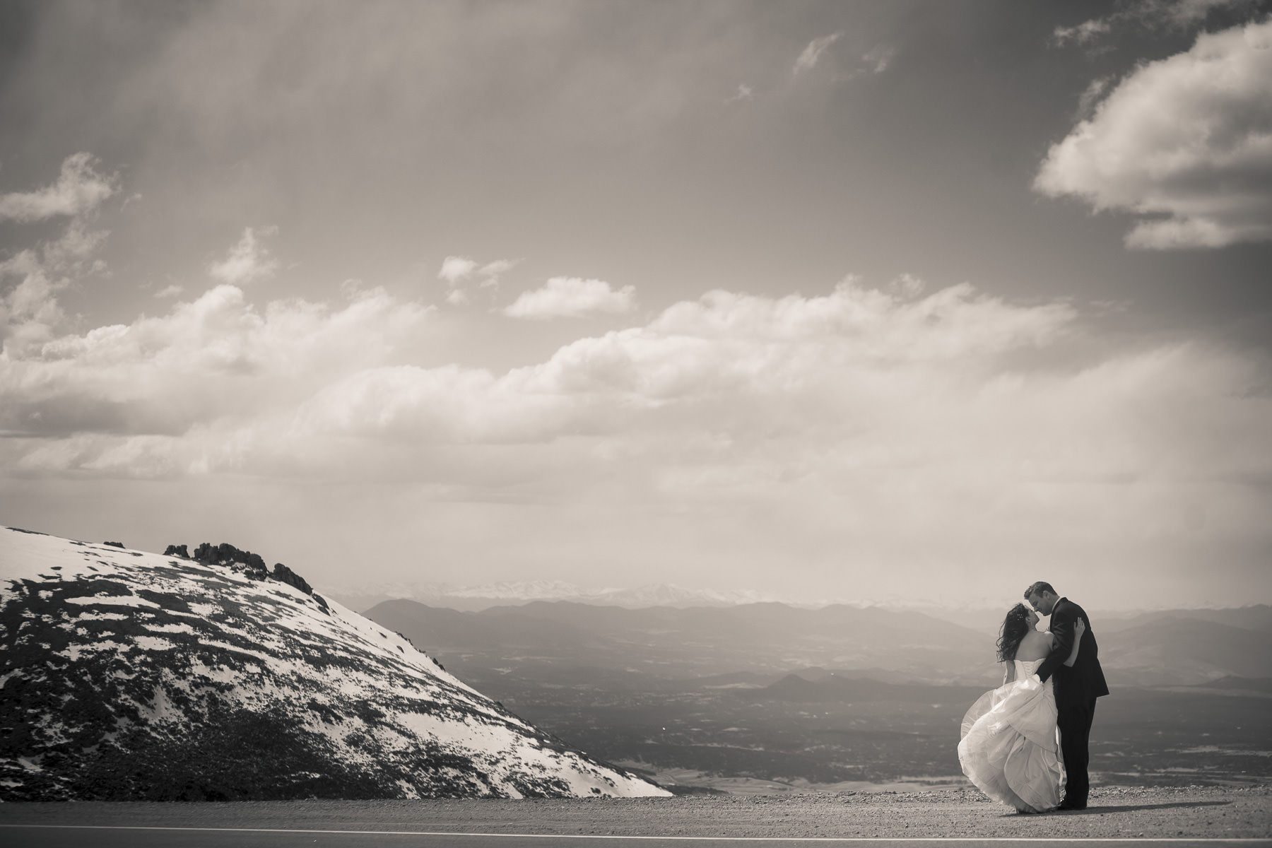 Black and white of bride and groom kissing overlooking Woodland Park from the Devil's Playground on the Pikes Peak Highway.