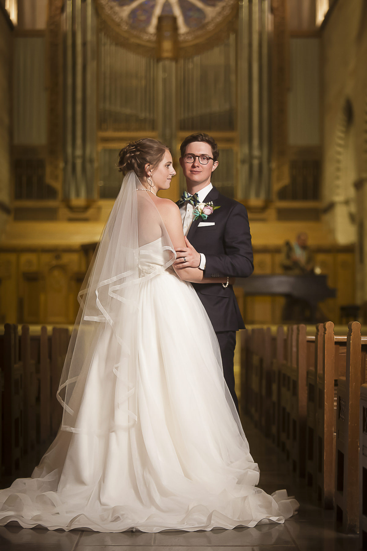 Bride and groom full-length portrait in the aisle after their Shove Chapel wedding celebration