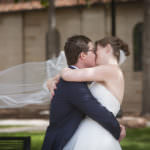 Bride and groom embrace and kiss outside of Shove Chapel.
