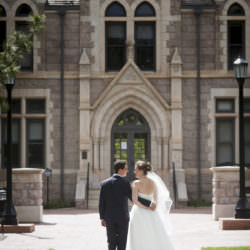 Bride and groom walking together towards Cutler Hall on the campus of Colorado College.