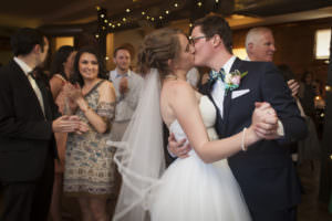 Bride and groom kiss on the dance floor as wedding guests look on at The Warehouse Restaurant.