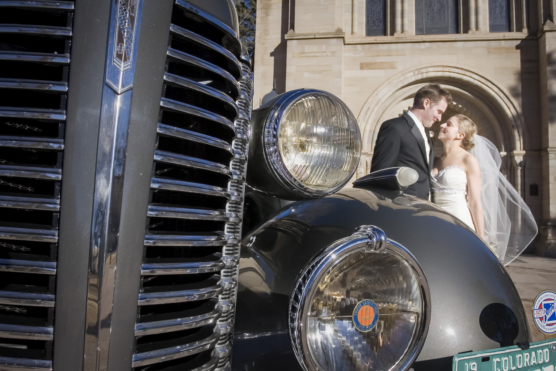Bride and groom stand in front of Buick with Shove Chapel behind.