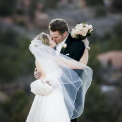 Bride and groom kissing with veil and bouquet.