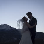 Bride and groom embracing in front of Pikes Peak at sunset.